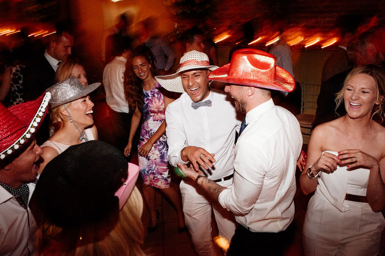 Crazy hats on the dance floor at a wedding