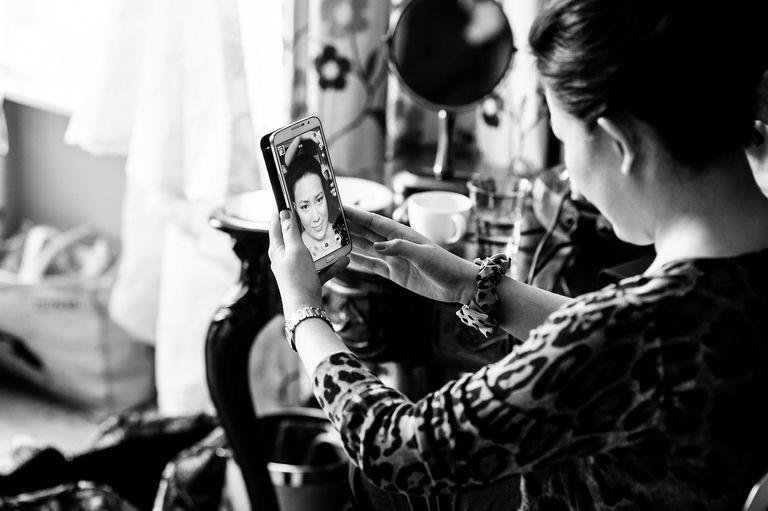 Bridesmaid checking make up in phone