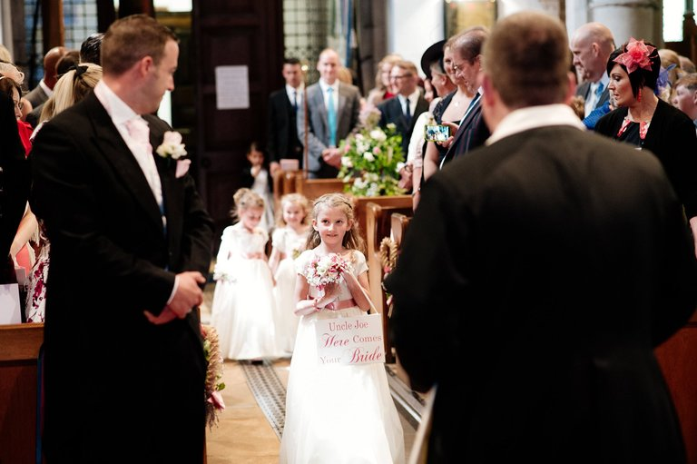 Flower girl walking down aisle with sign