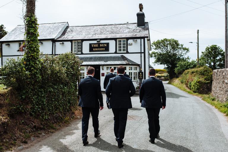 Groom walking to the pub before wedding