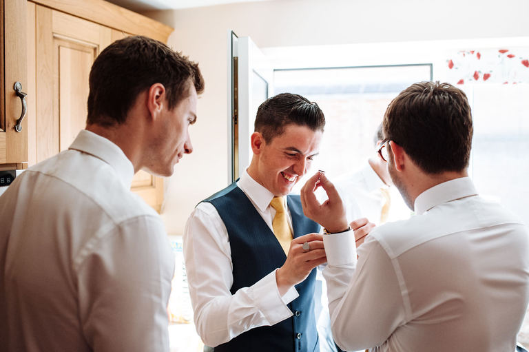 groom helping usher with cufflinks