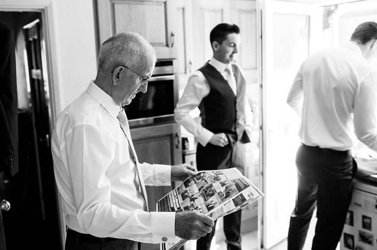 father of groom reading newspaper