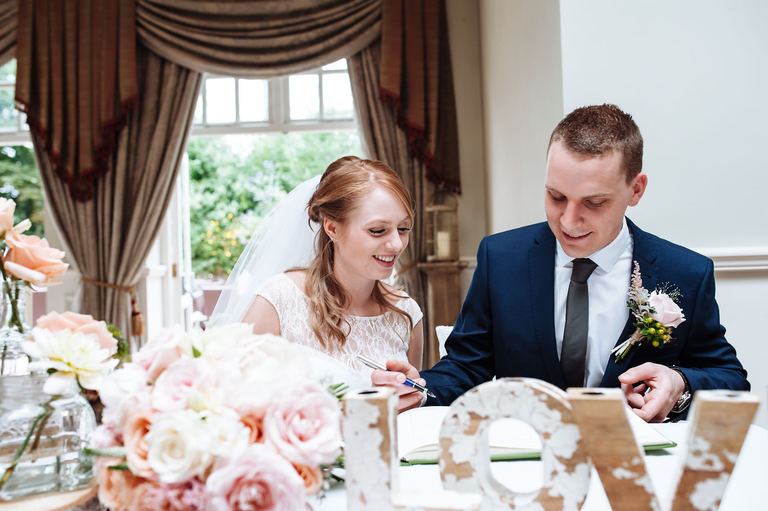 Bride and groom signing the register