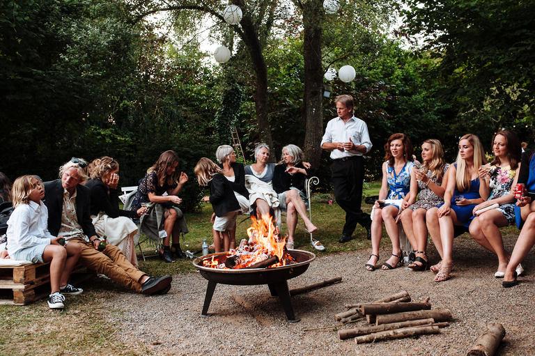 wedding guests sat around a fire