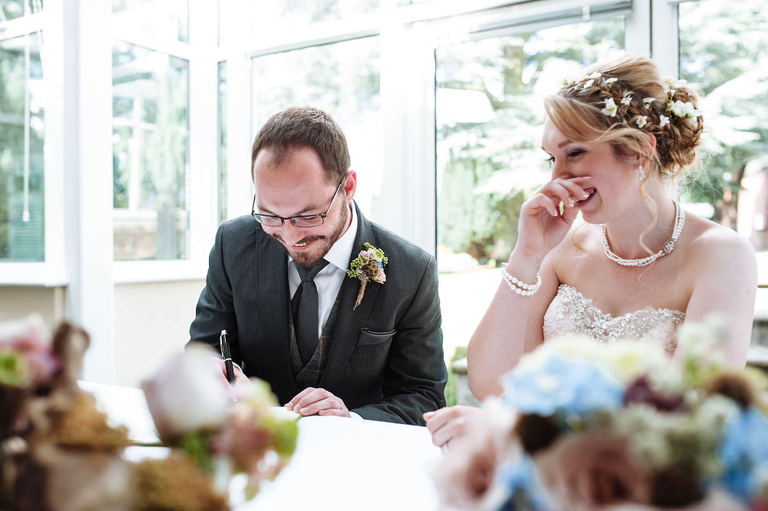 laughing bride as groom signs register