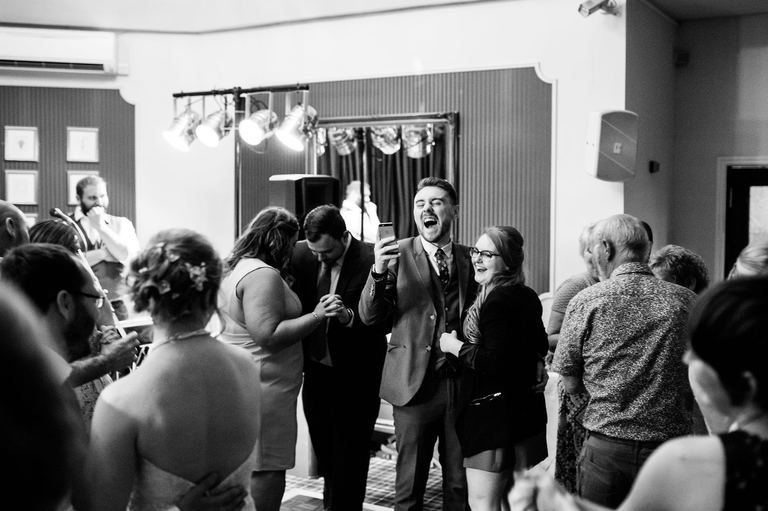 wedding guest laughing with phone on dancefloor