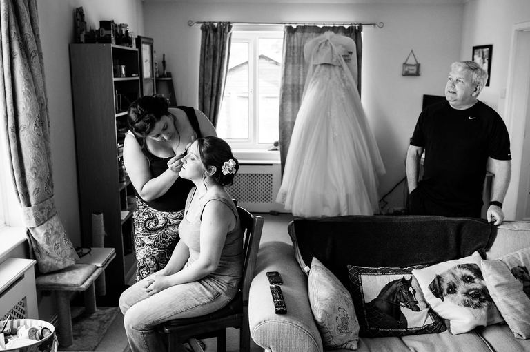 bridesmaid having make up done with wedding dress hanging up