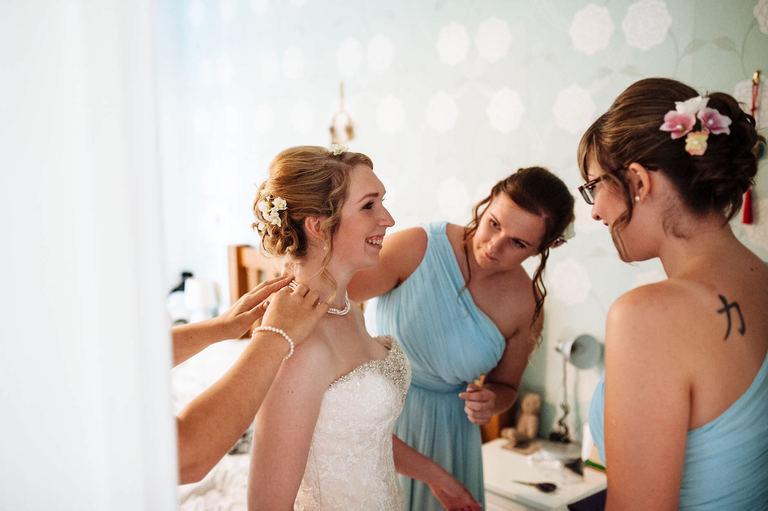 bridesmaids helping bride with necklace