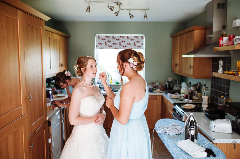 bride having make up done in the kitchen