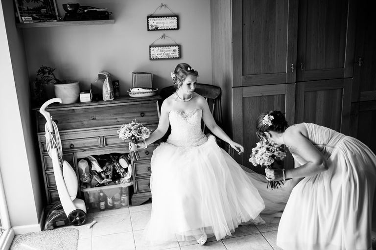 bridesmaid helping bride with her shoes