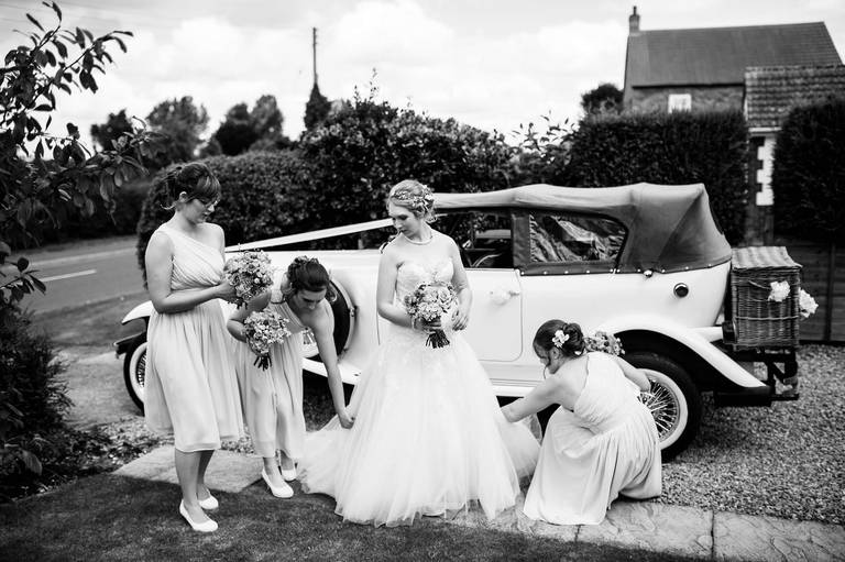 bride and bridesmaids by the wedding car
