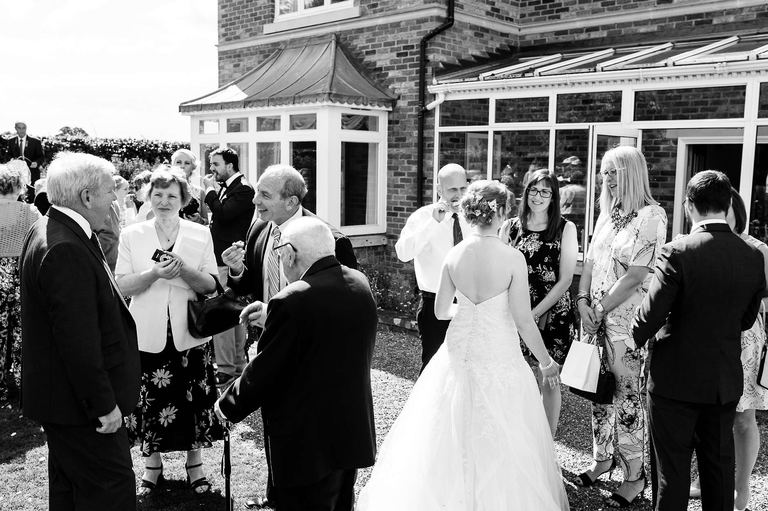 bride mingles with guests on the lawn
