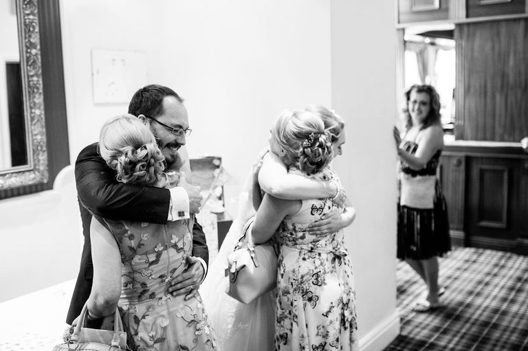 bride and groom hugging guests in the receiving line