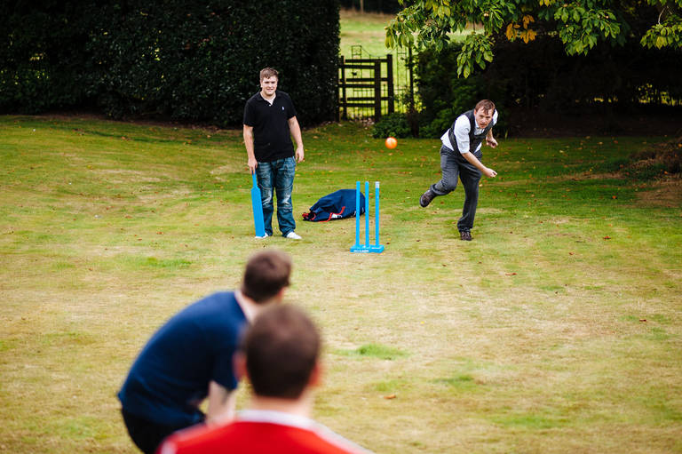 groom playing cricket with guests