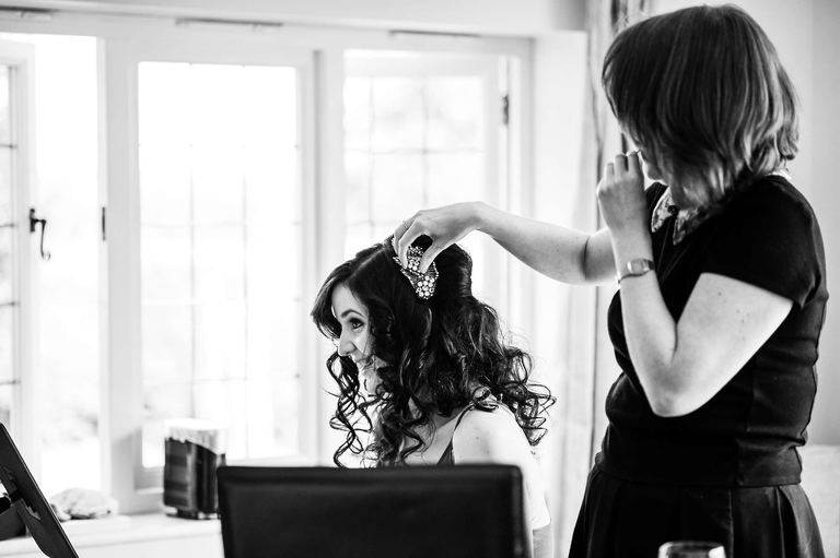 smiling bride having her hair curled