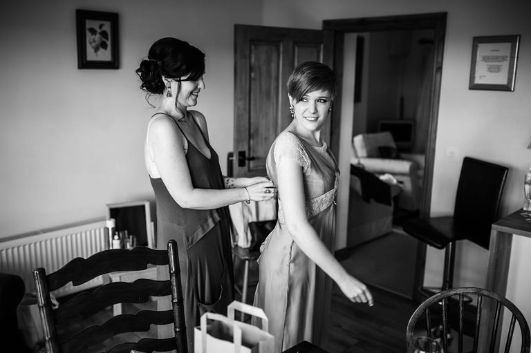 bride helps bridesmaid with her dress