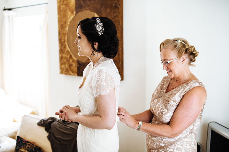 bride's mum helps her with her dress