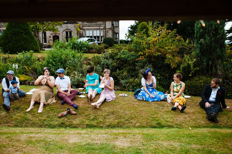guests in vintage dress sat on a grass bank