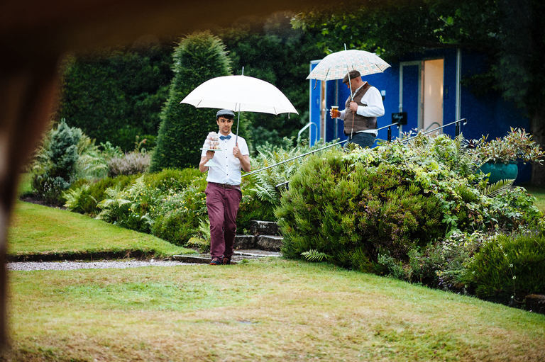groomsmen with umbrellas carrying supplies
