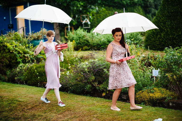 bridesmaids with umbrellas carrying supplies