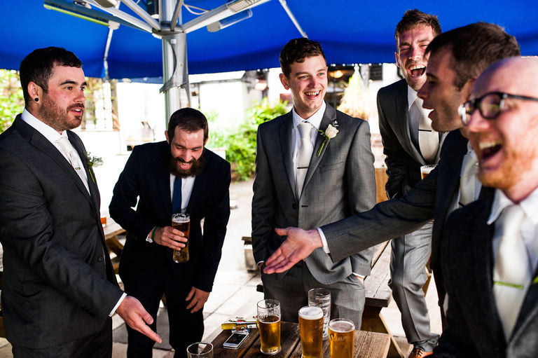 groom and groomsmen having a pre-wedding pint