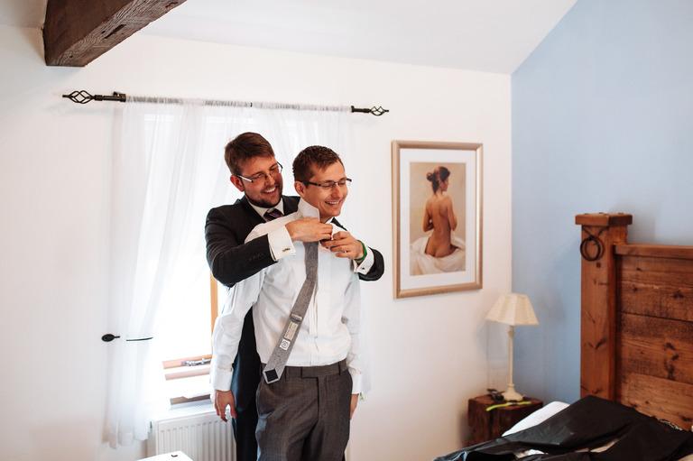 groomsmen help each other with ties