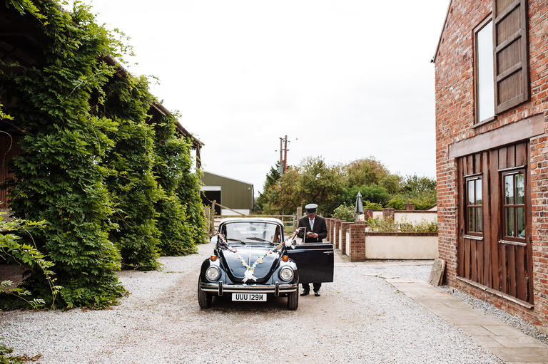 chauffeur waits with the wedding car
