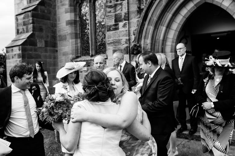 bride receives hug from bridesmaid