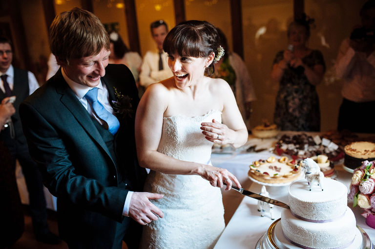 laughing while cutting the cake