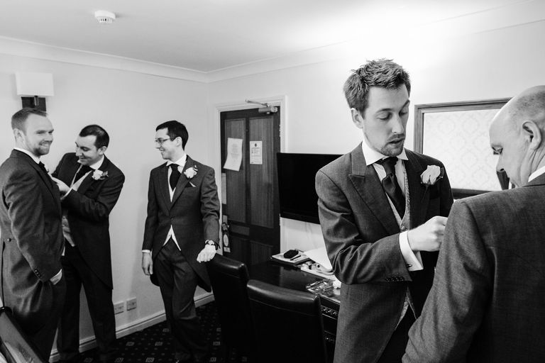 groomsmen attaching button holes