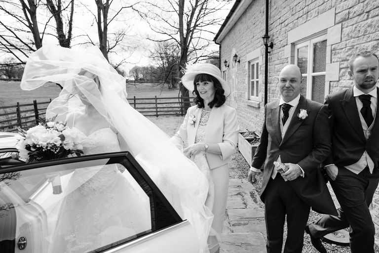 parents help their daughter into wedding car