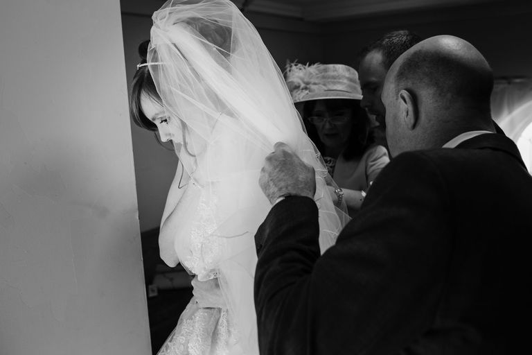 bride's family help with veil