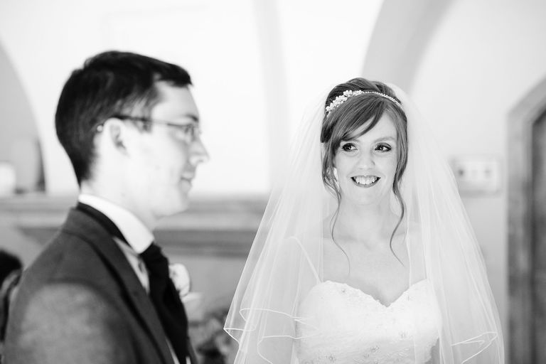 bride smiling at groom at the altar
