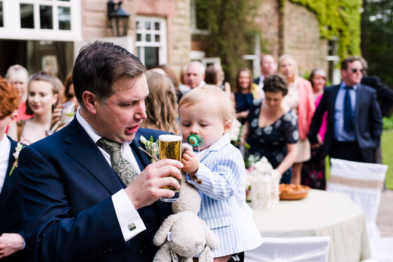 groom shares a drink with his son