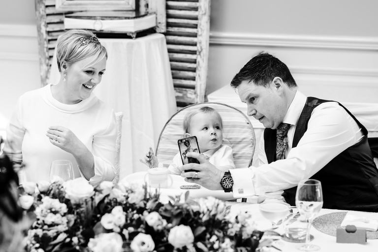 bride and groom take selfie with son