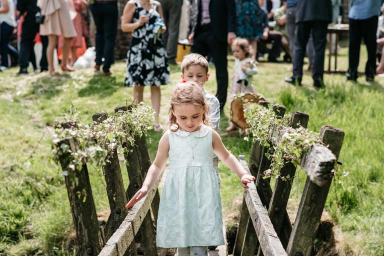 little girl crossing a bridge
