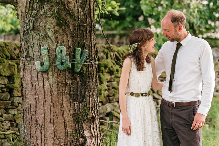 couple next to their initials on a tree