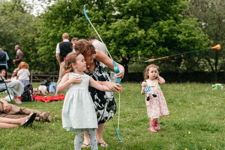 mum playing with her daughter and a toy bow and arrow