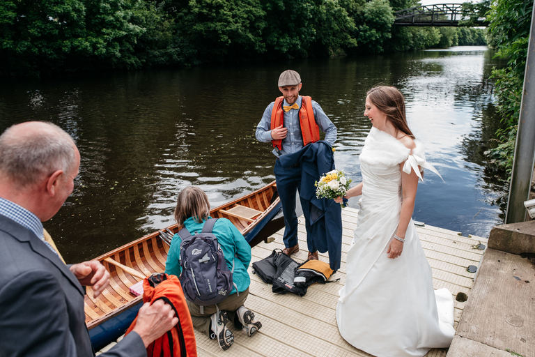 bride and groom arriving at venue by canoe