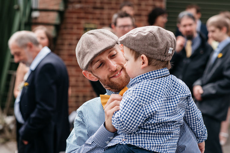 groom in flat cap holding a little boy