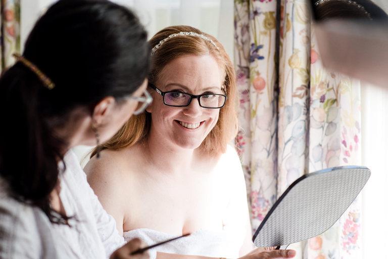 bride smiling at her make up artist