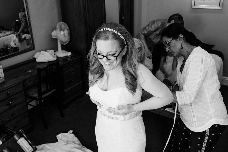 bride having her dress fastened