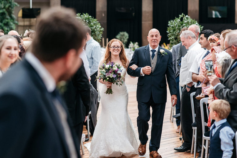 bride walks down the aisle with proud father