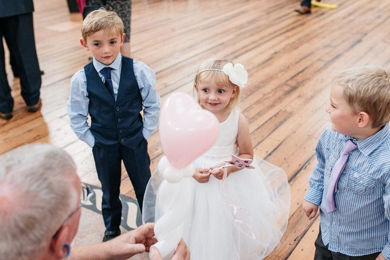 balloon man makes heart balloon for little girl