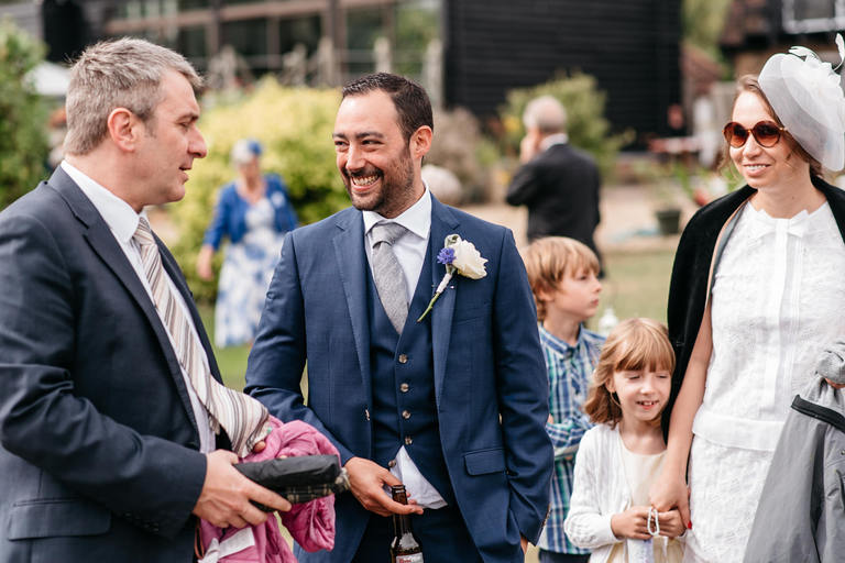 groom greeting guests as they arrive
