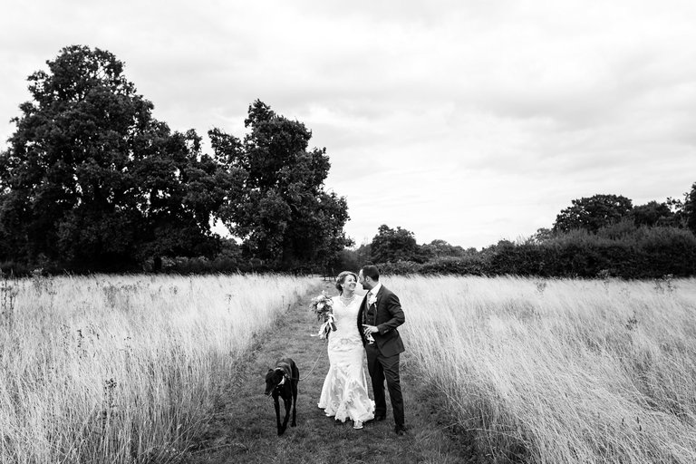 bride and groom with their dog in a field