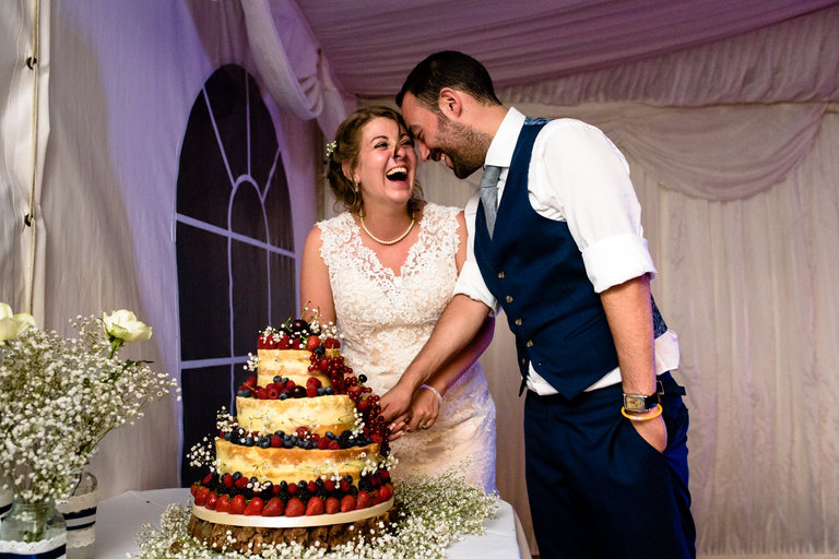 couple laughing while cutting the cake