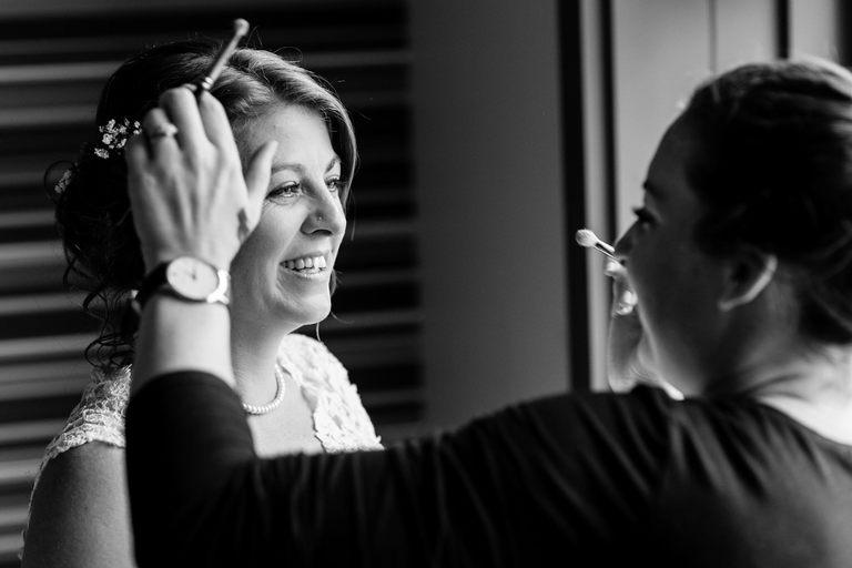 smiling bride having her make up applied