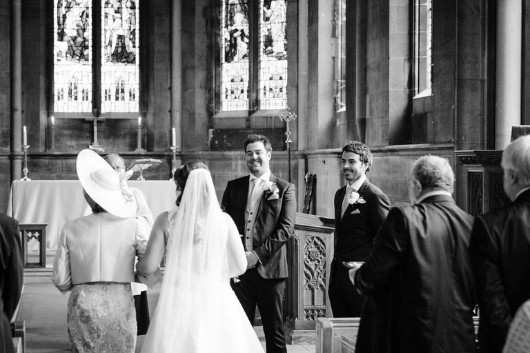 groom smiling as his bride walks down the aisle