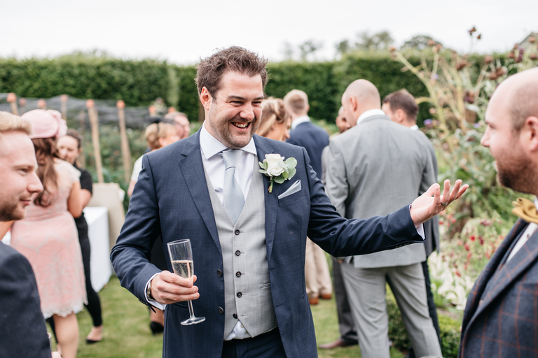 laughing groom with a glass of champagne